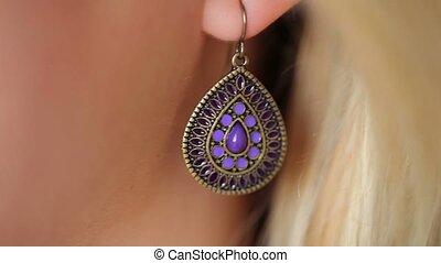 Earring in woman's ear closeup