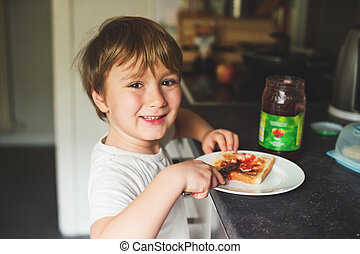 Cute little 6 year old boy preparing alone his toast with...