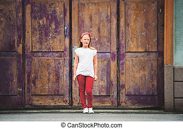 Outdoor fashion portrait of 8-9 year old girl walking down...