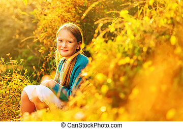 Outdoor portrait of a cute little 8-9 year old girl at...
