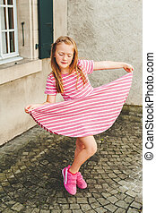 Outdoor portrait of adorable 6 year old girl wearing pink...