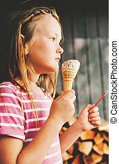 Cute little 6 year old girl eating ice cream outdoors,...