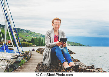 Middle age woman resting by the lake, using tablet pc...