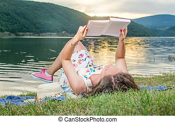 Woman reading a book by the lake. Solo relaxation