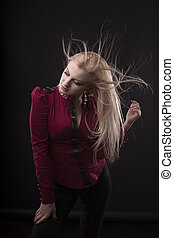 Glorious young woman with fluttering  hair posing at studio