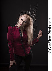 Stylish young woman with fluttering  hair posing at studio