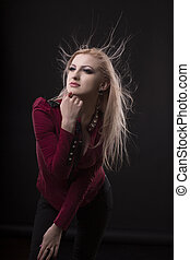 Fashionable young woman with fluttering  hair posing at studio