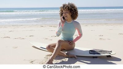 Female talking on phone on beach - Smiling female talking on...