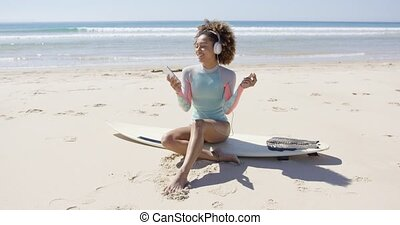 Female listening music on beach sitting on surfboard on sea...