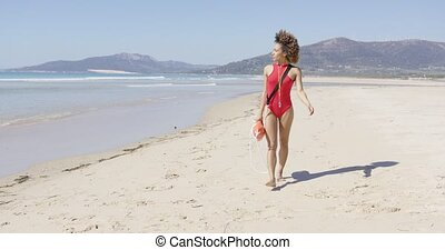 Female lifeguard walking along beach - Female lifeguard...