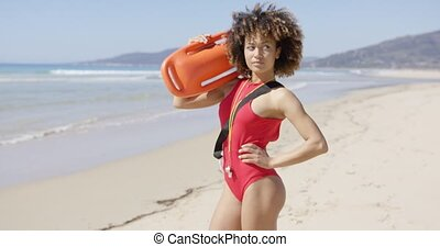 Female posing with rescue float on beach - Female lifeguard...