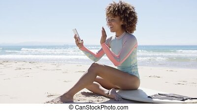 Smiling female on beach using smartphone - Smiling female...