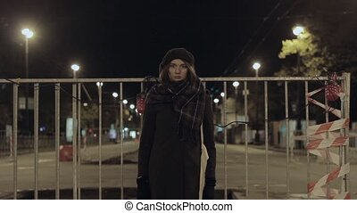 Woman stand in front of road prohibited blocking fencing, night city traffic