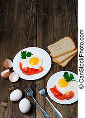 healthy breakfast: fried egg on wooden table and three slices of bread with greens, eggs, tomatoes and pepper
