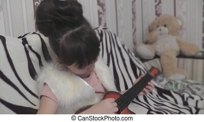 Girl playing the guitar and sitting behind the Teddy bear