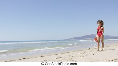 Lifeguard female with rescue float walking on beach and...
