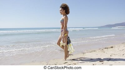 Female with flippers standing on beach - Smiling female...