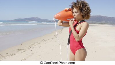 Lifeguard blowing a whistle holding rescue float - Lifeguard...