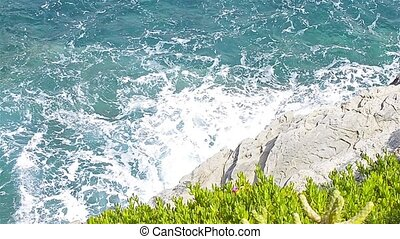 Strong sea waves beating against rocky shore in stormy windy...