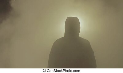 Male silhouette in hood jacket stand in white steam cloud...