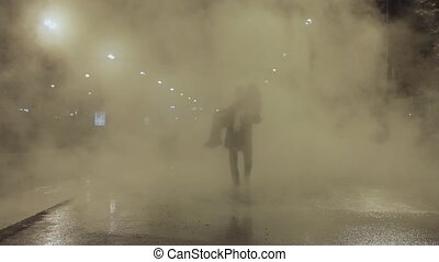 Man carry woman trough white steam cloud on night city street and kiss her