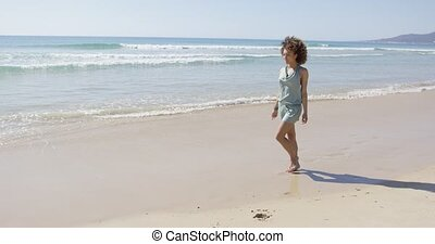 Female walking along the shore of beach - Female walking...