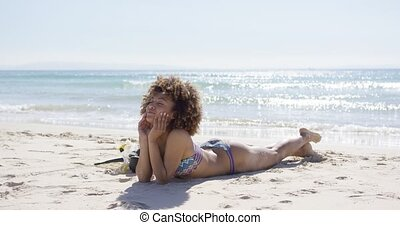 Smiling female sunbathing on beach - Smiling female...