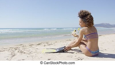 Female with flippers sitting on beach - Female with flippers...
