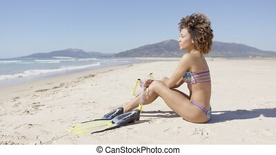 Female sitting on beach with flippers - Female wearing...