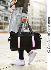 Close up of black leather bag accessory in hand of fashion woman . Black short dress