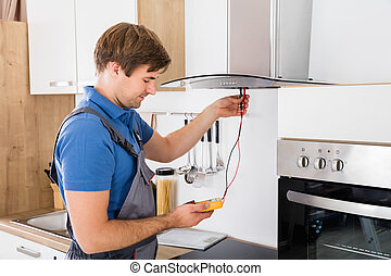 Repairman Checking Kitchen Extractor Filter - Young Male...