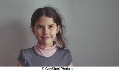teen school girl smiling on a gray background indoor the...