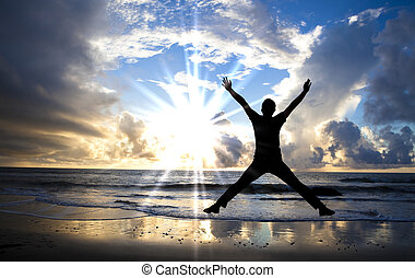 happy man jumping on the beach with beautiful sunrise