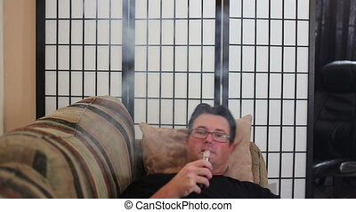 Man vaping at home two - Man sitting on sofa at home using...