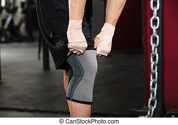 Person Wearing Knee Bandage - Close-up Of A Person Preparing...