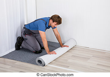 Handyman Rolling Carpet On Floor - Young Male Handyman...