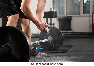 Weightlifter Hand Applying Talc Powder Before Doing Exercise...
