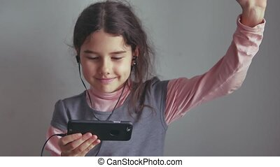 Teen girl listening to music on headphones and dancing on a smartphone