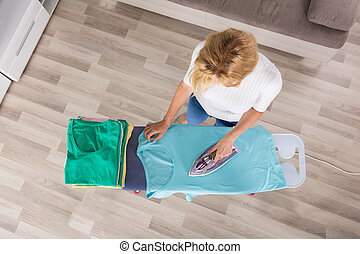 High Angle View Of Woman Ironing Clothes On Ironing Board At...
