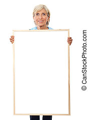 Senior businesswoman holding placard - Senior smiling...