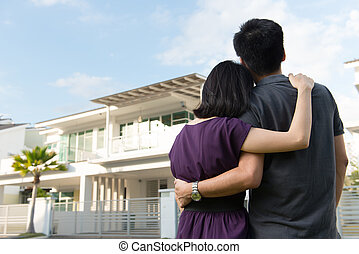 Family with dream house - Couple standing in front of dream...