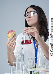 Medicine and Research Ideas. Laboratory Female Staff Dealing with Apple Specimen and Test Liquid in Flask.