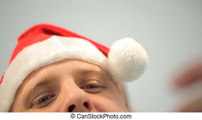 Young man with ginger eyebrows in cap of Santa secures top garlands.