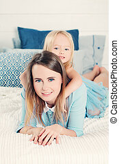 Smiling Mother with Daughter Lying on the Bed at Home. Happy Family
