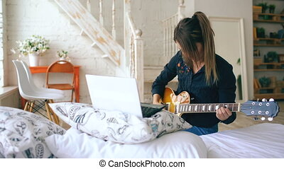 Attractive young girl learning to play electric guitar with...