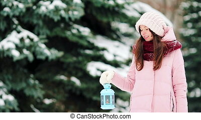 Happy woman with candlelight in cold winter outdoors - Young...