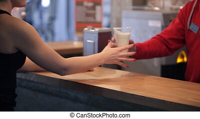 Barman in fitness center give protein shake to young slim...