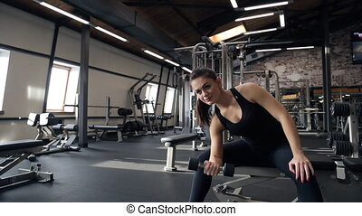 Young pretty slim woman do exercise with dumbbell in gym....
