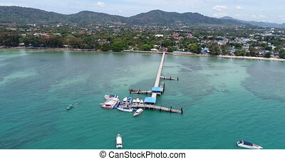Aerial drone footage approaching pier on Rawai beach in...
