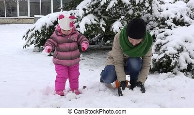 woman with daughter throw snowballs. Happy family girls....